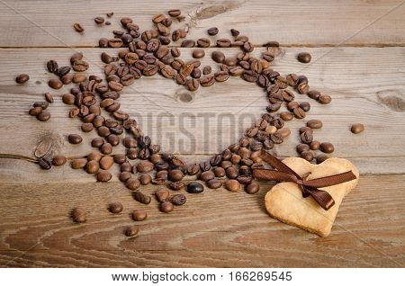 Frame- Heart From Coffee Beans And Two Cookies-heart Related Together On Wooden Table