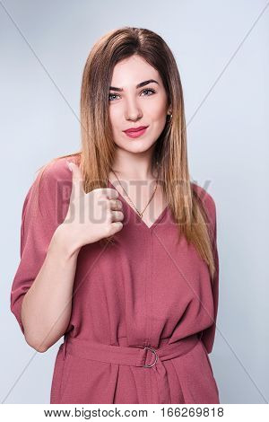 Portrait of smiling beautiful woman showing thumbs up gesture over blue background.