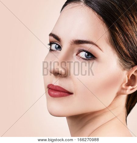 Beautiful woman with healty fresh skin looking around over beige background. Spa concept.