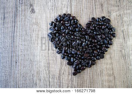 Coffee beans make into Heart shape on wood background Coffee beans on wood background. Shape of word Coffee made from coffee beans, decorated with  heart on wooden surface. Roasted coffee beans on rustic wood background.