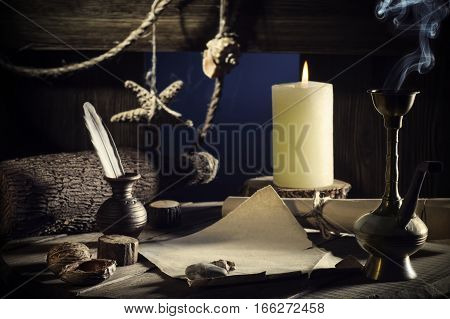 Vintage concept of sea travel writing a letter on a wooden keg with a burning candle smoking a hookah. Message in a bottle on old paper. Cabin wooden vessel close-up a pirate ship. Sea adventure.