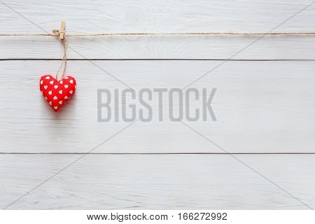 Valentine background with single sewed pillow diy handmade heart on red clothespins at rustic white wood planks. Happy lovers day card mockup, copy space
