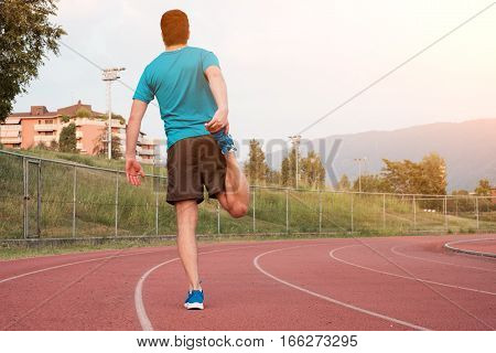 Runner making stretching on the race track