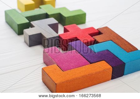 Abstract Background. Different colorful shapes wooden blocks on white wooden background. Geometric shapes in different colors. Concept of creative logical thinking or problem solving. Copy space.