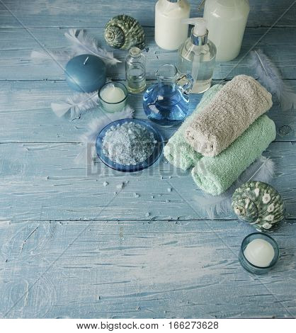 Set for spa with towels, salt and aromatic oils, candles and seashells on a wooden blue background, selective focus, space for text