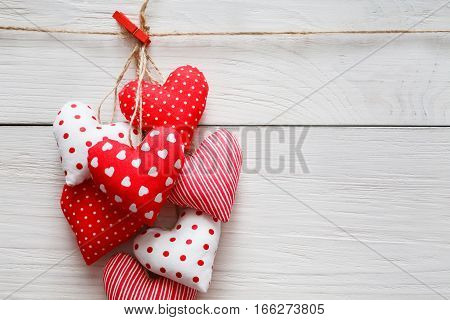Valentine background with sewed pillow diy handmade hearts bunch on red clothespins at rustic white wood planks. Happy lovers day card mockup, copy space