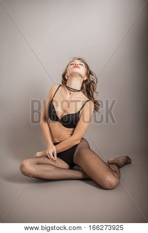 beautiful sensual luxury woman in lingerie posing on gray background