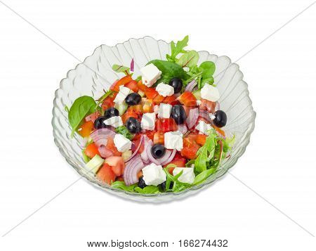 Greek salad in a glass salad bowl on a white background.