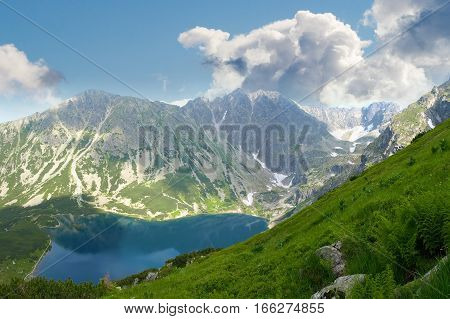 Top view of a mountain lake on the background of the craggy mountain slopes and sky with clouds and grass on the foreground