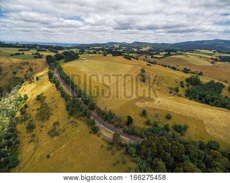 Aerial View Of Australian Coutryside - Yellow Fields, Hills, And Rural Road