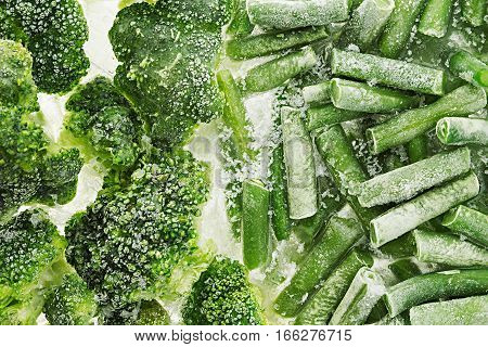 Fresh frozen green french bean and broccoli with hoarfrost closeup as background. Healthy vitamin food.