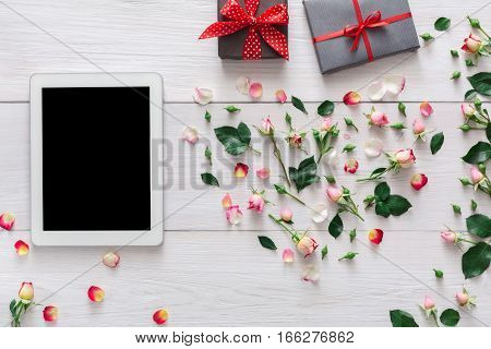 Valentine day internet sales concept, online shopping holiday background. Tablet screen with copy space on white wood with rose flowers heart and gift boxes, top view. Advertising mockup