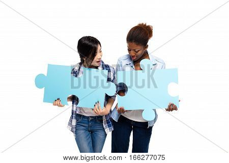 Two Friends Of Different Ethnicity With Puzzle Pieces On White