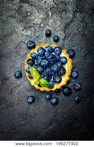 Tart with lemon cream and fresh berries on black background, top view