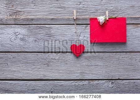 Valentine background with red paper heart and empty greeting card on clothespins on rustic wood planks. Happy lovers day card mockup, copy space