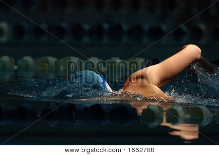 A male swimmer swims the freestyle