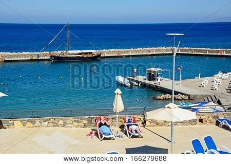 AGIOS NIKOLAOS, CRETE - SEPTEMBER 17, 2016 - Tourists relaxing on the Hotel Mirabello sun terrace with the harbour to the rear Agios Nikolaos Crete Greece Europe, September 17, 2016.