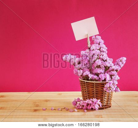The sweet statice flower in basket with blank paper label on red pink background and wooden table romance concept