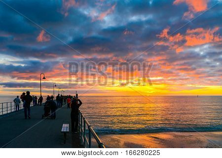 Adelaide, Australia - August 16, 2015: People walking on Glenelg Beach jetty at sunset South Australia