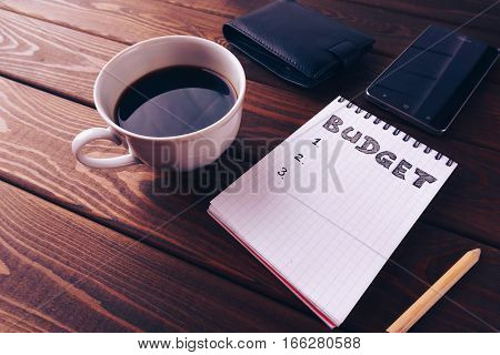 Budget list on notepad, mobile phone, pouch and cup of coffee on dark wooden table. Budget planing concept. Vintage style, retro toned picture.