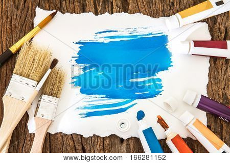 Art brush and blue watercolor painted with white paper art on wooden background