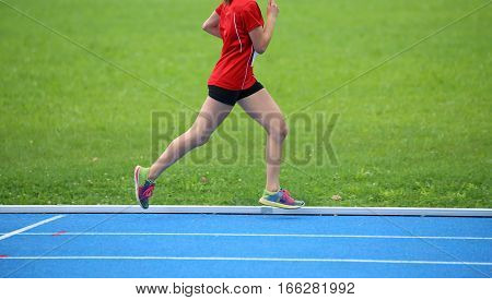 young girl athlete running on the color athletics track