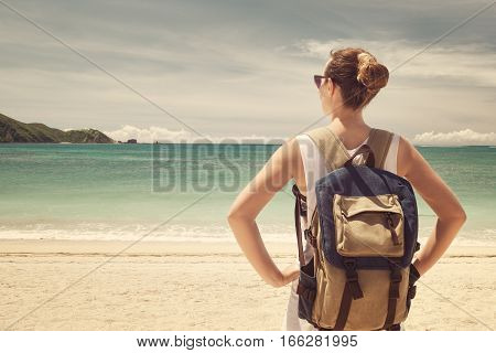 Happy young traveler with a backpack, enjoying the view of a tropical beach on a background the mountains. Young backpacker traveling along Asia, happy female walking discovering world, summer vacation concept