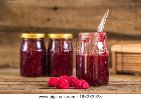 Raspberry jam in a jar on the wooden table