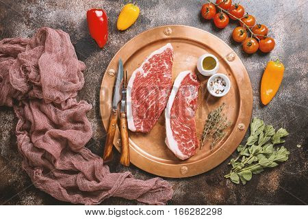 Fresh raw Prime Black Angus beef strip steaks on metal plate over dark rustic concrete background, top view. Ingredients set for making healthy dinner.
