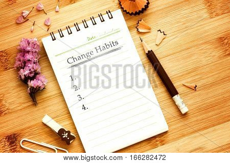 notepad with pencil on wooden table for change habits list concept overhead shot or Top view