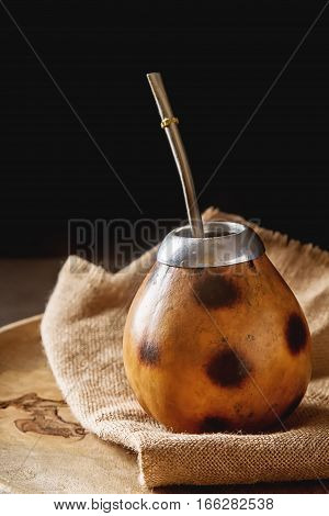 Traditional South American yerba mate tea in the calabash circle and Bombilla. Dark background