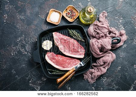 Fresh raw Prime Black Angus beef strip steaks on grill pan over dark rustic concrete background, top view. Ingredients set for making healthy dinner.