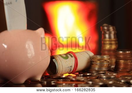 Austerity heating in the fireplace saving money in a piggy bank