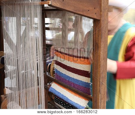elderly weavers with an old hand loom during the weaving of the fabric with the old techniques of the last century