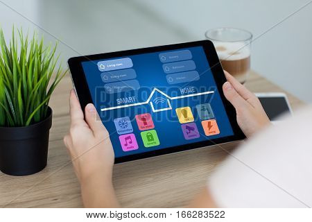 woman holding tablet computer with app smart home in room