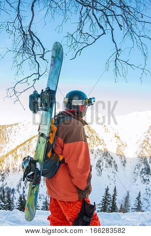 Freerider Man Is Standing On The Mountainside In A Helmet And With A Backpack And Looks Into The Dis