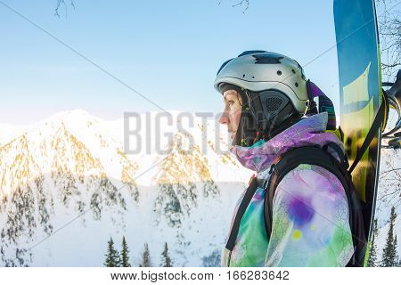 Freerider woman is standing on the mountainside in a helmet and with a backpack and looks into the distance.