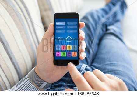 man lying on sofa and holding phone with app smart home