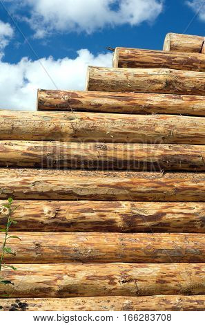 Construction of rural house from logs on a background of blue sky with clouds. Vertical view