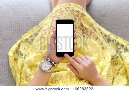 woman in yellow dress with jewelry on hand holding phone with isolated screen