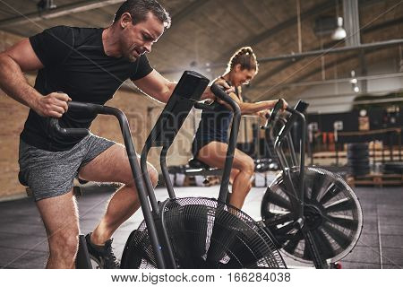 Young man and woman exercising on cardio bikes in gym