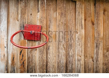 The old basketball ring attached to a wooden wall. The place for the text