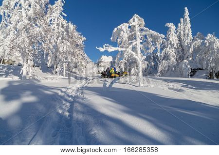Walk on a snowmobile through forests and fields of the Ural Mountains. Athletes resting below the top of the mountain.
