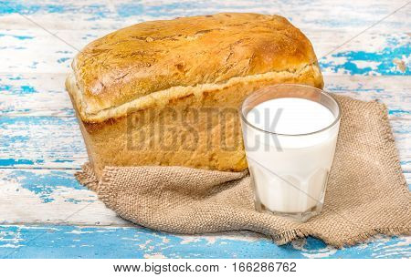 Glass of milk with bread on old wooden table.