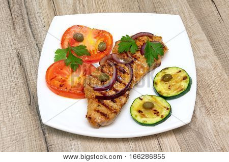 grilled meat with vegetables on a wooden background. horizontal photo.