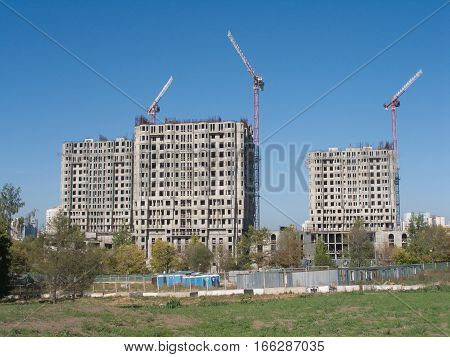 Long hoisting tower cranes in construction new apartment building process over cloudless sky