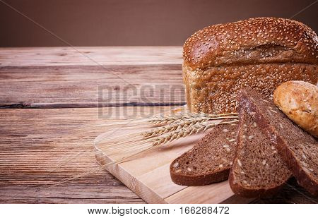 Fresh bread, sweet pastries, ears of ripe wheat, baked goods, harvest on the farm, lots of baked goods, close-up bread, wood grain