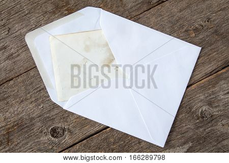 White envelope with blank card on wooden background