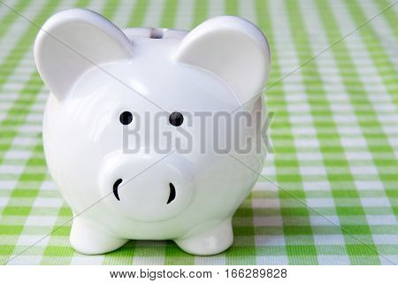 Close-up of piggy bank on the table with checkered tablecloth