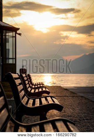 A tranquil sunset view of benches looking over Lake Garda Italy towards the Italian Alps.